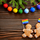 Christmas background of gingerbread man with flag spruce branches and colorful balls on wooden table - PhotoDune Item for Sale