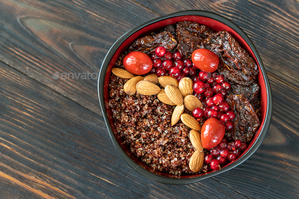 Bowl of red quinoa with nuts and sun-dried tomatoes - Stock Photo - Images