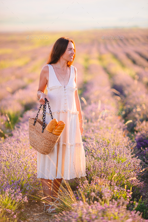 Woman in lavender flowers field in white dress and hat - Stock Photo - Images