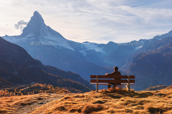 Picturesque view of Matterhorn peak and tourist sitting on wooden bench - Stock Photo - Images