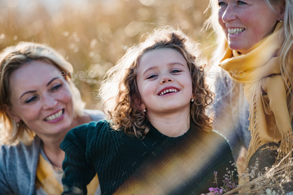 Portrait of small girl with mother and grandmother resting in autumn nature - Stock Photo - Images