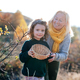 Small girl with grandmother collecting rosehip fruit in autumn nature - PhotoDune Item for Sale