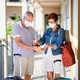 Senior couple with face masks and luggage outside apartment on holiday - PhotoDune Item for Sale