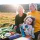 Small girl with mother and grandmother having picnic in nature at sunset - PhotoDune Item for Sale