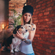 A stylish tattoed blonde female in t-shirt and jeans embraces two cute dogs. - PhotoDune Item for Sale