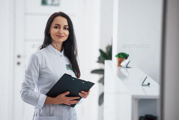 Portrait of brunette doctor with notepad in hands that stands indoors at clinic - Stock Photo - Images