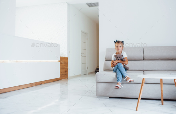 Cute little girl with teddy bear in hands sits in waiting room of hospital - Stock Photo - Images