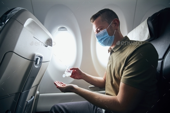 Man wearing face mask inside airplane - Stock Photo - Images