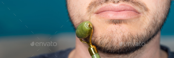 Bearded man is using jade face roller - Stock Photo - Images