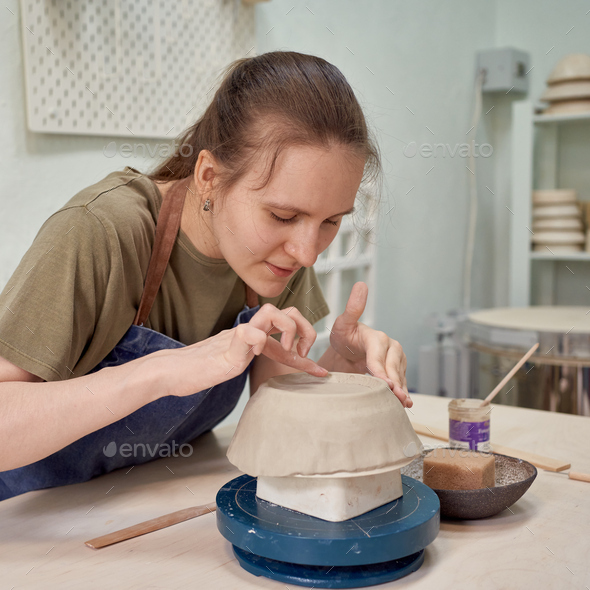Delight female apprentice working on pottery bowl in workshop - Stock Photo - Images