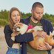 Young happy couple of man and woman with corgi dog, beautiful female biting ears of puppy - PhotoDune Item for Sale