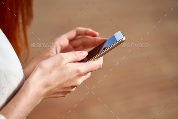 Faceless young woman is holding smartphone and typing - Stock Photo - Images