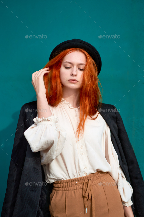 Redhead woman is resting against bright green wall - Stock Photo - Images