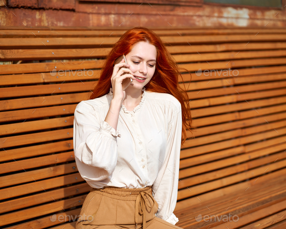 Red-haired woman talking on cell phone. Beautiful stylish fashion model - Stock Photo - Images