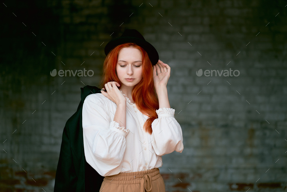 Redhead woman is resting against dark grunge wall. Female in black hat - Stock Photo - Images