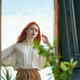 Beautiful red-haired woman looks at reflection in mirror on street - PhotoDune Item for Sale