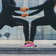 Athletic couple is stretching over modern building background. - PhotoDune Item for Sale