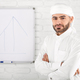 Handsome young muslim male in traditional Islamic clothing standing in front of financial chart - PhotoDune Item for Sale