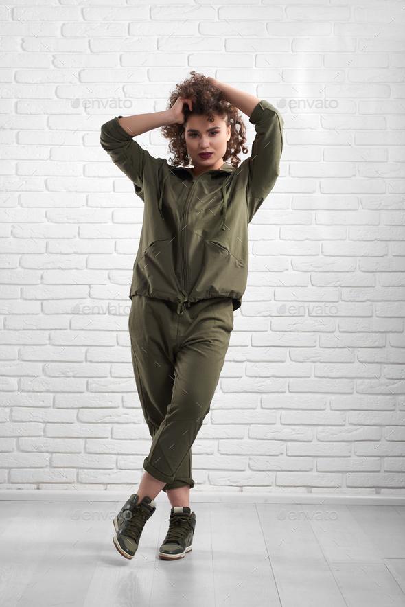 Exotic model demonstrating green modern sportsuit - Stock Photo - Images