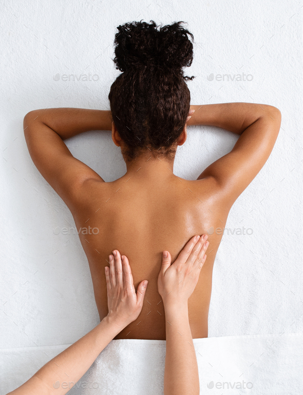Therapist massaging african woman back, top view - Stock Photo - Images