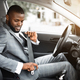 Handsome black businessman fasten seat belt in his car - PhotoDune Item for Sale
