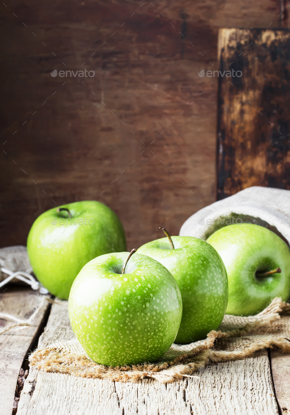 Green apples on vintage wooden background, selective focus - Stock Photo - Images