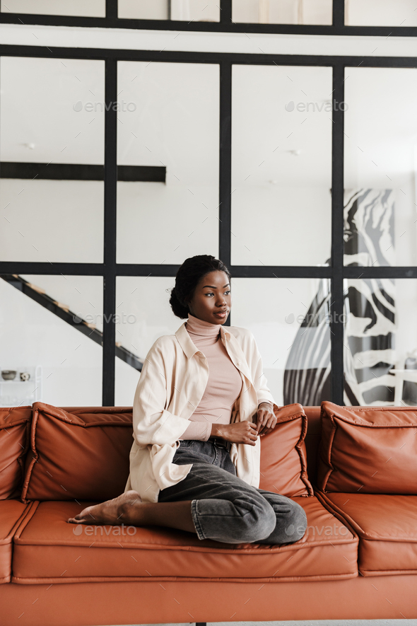 Attractive young smiling african woman sitting on a couch