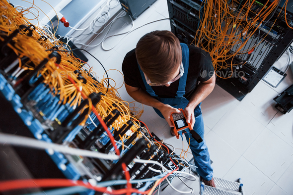 Young man with measuring device that works with internet equipment and wires in server room - Stock Photo - Images
