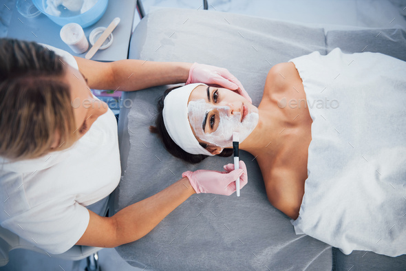 Close up view of woman that lying down in spa salon and have face cleaning procedure by the mask
