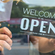 Close-up of the Business owner hand holding an open sign for service. - PhotoDune Item for Sale