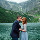 young couple on a walk near the lake surrounded by the mountains - PhotoDune Item for Sale