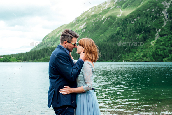 young couple on a walk near the lake surrounded by the mountains - Stock Photo - Images