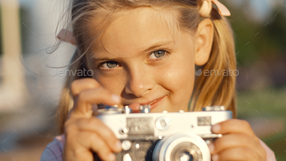 Smiling little girl with a retro camera - Stock Photo - Images