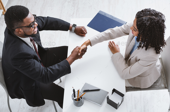 Above view of personnel manager shaking hands with vacancy applicant during job interview at office