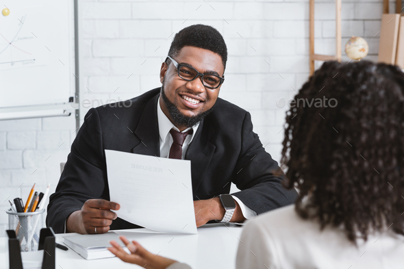 Happy personnel manager and young job applicant on work interview at company office