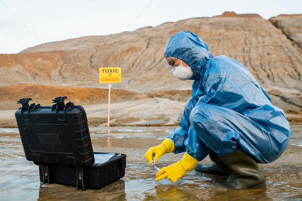 Contemporary young female ecologist putting sample of water into flask - Stock Photo - Images