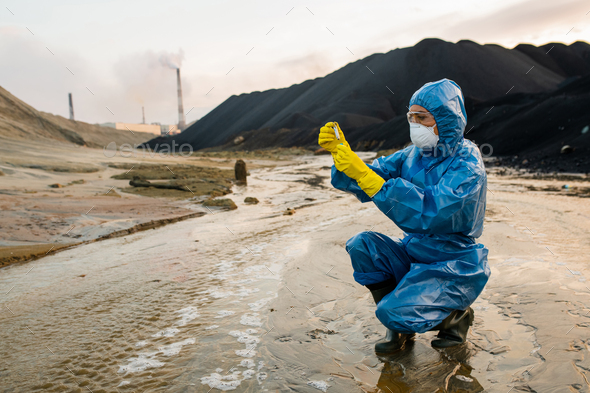 Contemporary female ecologist or researcher making experiments in toxic area - Stock Photo - Images