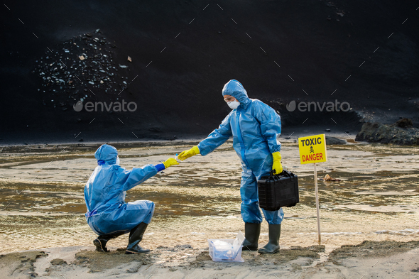 Young ecologist in protective workwear taking flask with sample of water - Stock Photo - Images