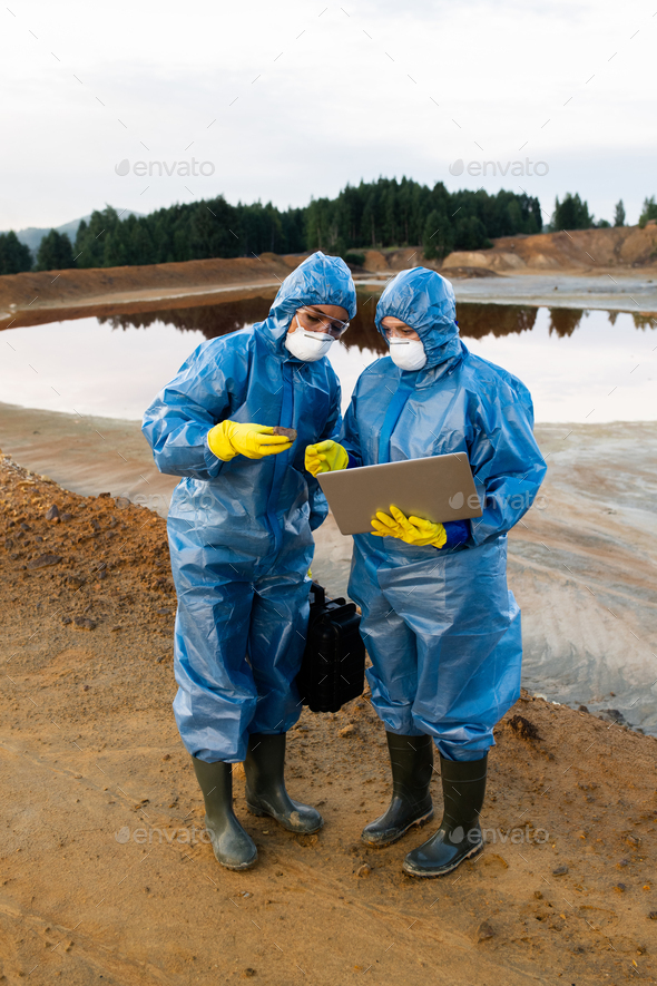Young female ecologists in protective workwear standing on polluted soil or clay - Stock Photo - Images