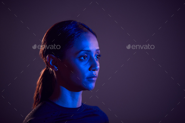 Studio Profile Shot Of Woman With Face Illuminated By Blue Light - Stock Photo - Images