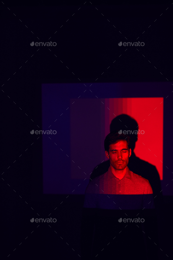 Studio Shot Of Man With Eyes Closed Illuminated By Red Light - Stock Photo - Images