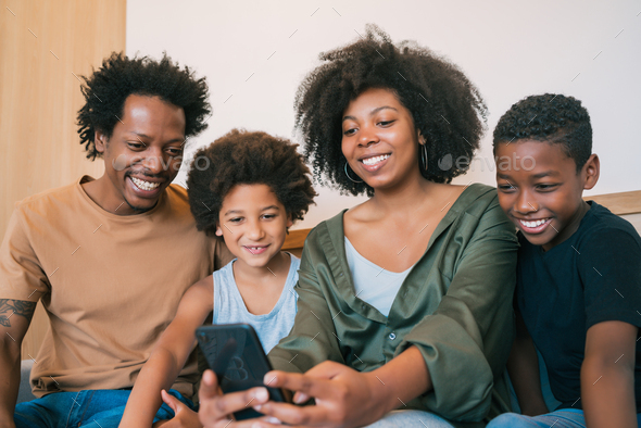 Family taking selfie together with phone at home. - Stock Photo - Images