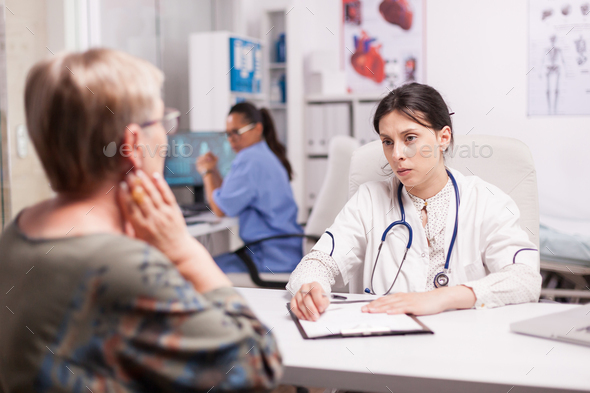 Young doctor examining senior patient - Stock Photo - Images