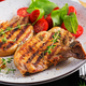 Grilled pork steaks and salad with tomatoes in plate on dark background. - PhotoDune Item for Sale