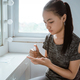 a teenage girl is cleaning her hands by spraying hand sanitizer - PhotoDune Item for Sale