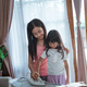 little girl try to help chores by holding the iron together with her older sister - PhotoDune Item for Sale