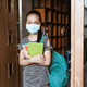 an Asian teenage girl standing wearing a mask and backpack carrying a book - PhotoDune Item for Sale