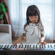 little girl learning to play a keyboard instrument in a room - PhotoDune Item for Sale