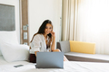 Beautiful smiling asian girl with long hair working on laptop on bed in the hotel room - PhotoDune Item for Sale