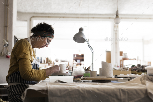 Woman making pottery in workshop - Stock Photo - Images